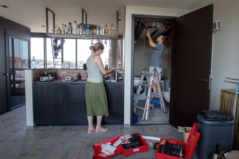 Firma IJskoud is bezig met het installeren van een airco bij de familie Hermes in Purmerend, Claudine Hermes zet een kopje koffie terwijl de monteurs bezig zijn rechts en links op het dak. Beeld Maartje Geels