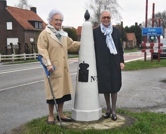 Denise Dobbelaere-de Baets (l) en Diana Danneels-de Baets bij de grenspaal in Eede, waar koningin Wilhelmina 75 jaar (en een dag) na vijf jaar ballingschap geleden terugkeerde in Nederland.