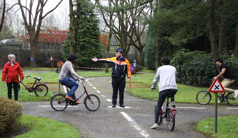 Een politieagent van zone Neteland laat de vluchtelingen veilig over het kruispunt fietsen in het verkeerspark.