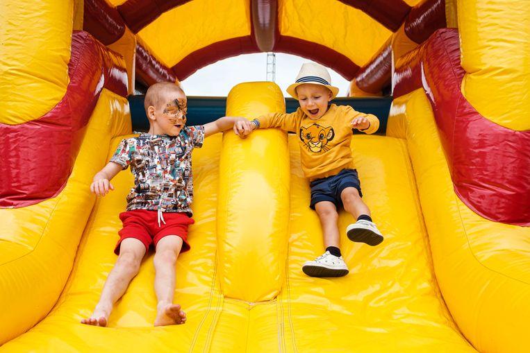 Ferre (6) en Tybo (3) amuseren  zich op de opblaasbare glijbaan. De opbrengst van een zomerfestival gaat naar hun moedige strijd tegen kanker.