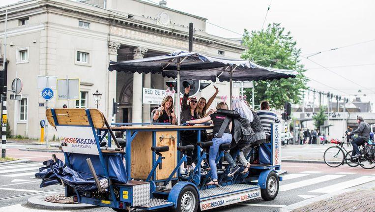 Toeristen op een bierfiets op het Haarlemmerplein Beeld Eva Plevier