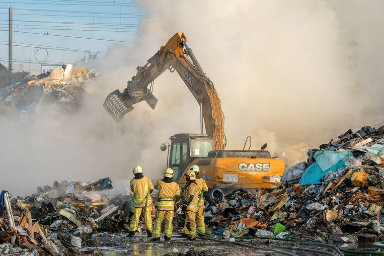 De brandweer haalt met een kraan de verschillende lagen afval weg en blust wat nog smeult.
