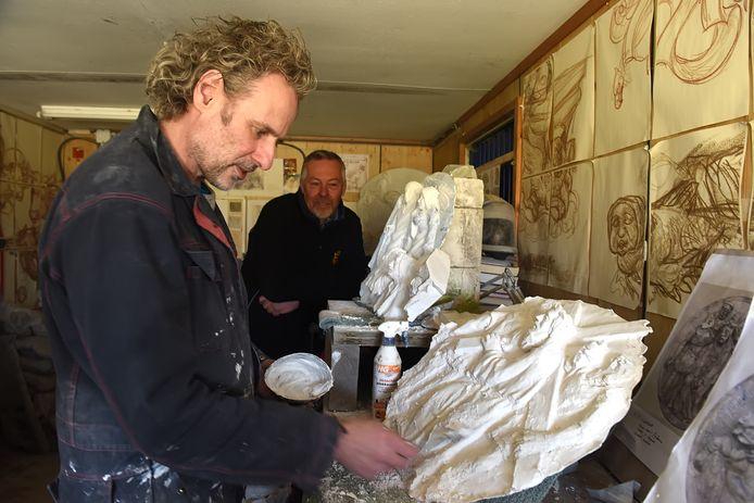 Serge van Druten werkt aan het herstel van de  Geheimen van de Rozenkrans in Hoogland.  Opdrachtgever Jac van Trijp (midden) van Dorpswerk Sprundel luistert op de achtergrond mee.