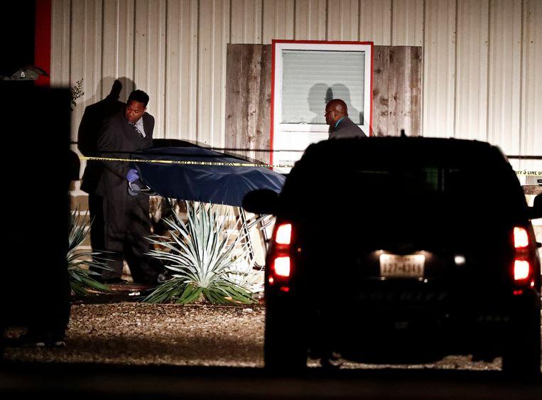 Een lichaam wordt weggedragen van de plek van de schietpartij.