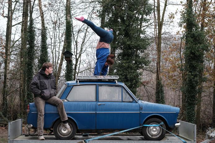 Jansje Bolder doet een handstand op de blauwe Daf terwijl haar man Rik toekijkt.
