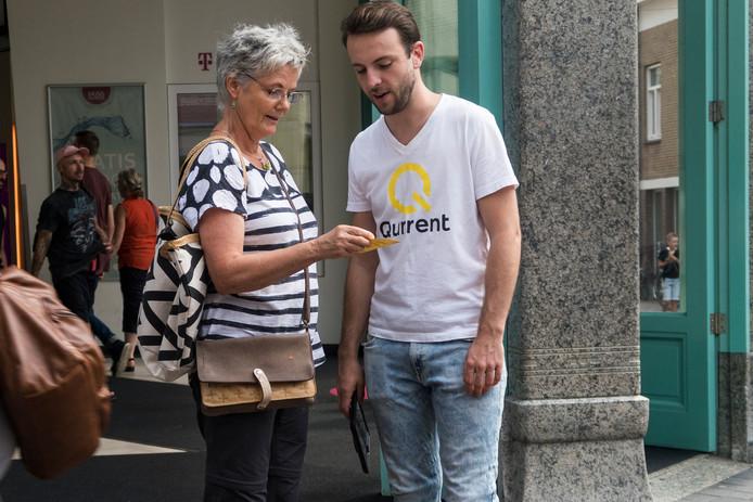 Een werver voor energiemaatschappij Qurrent probeert een vrouw te interesseren voor een energiecontract.
