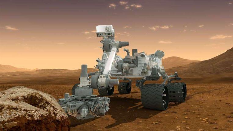 Impressie van de onderzoeksrobotwagen Curiosity aan het werk op Mars. Beeld afp