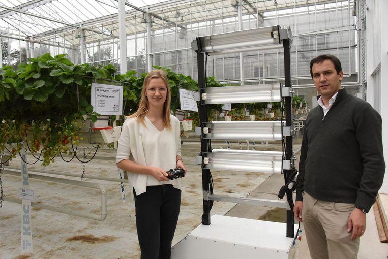 Onderzoekers Marieke Vervoort en Tom Coen bij de UV-belichtingsrobot.