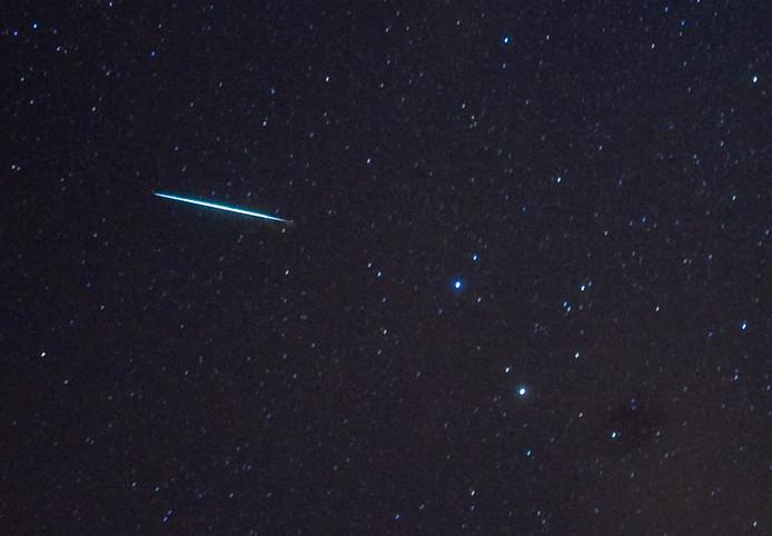 Een meteor van de Geminidenzwerm dringt door in de atmosfeer van de aarde langs de sterren Castor en Pollux.