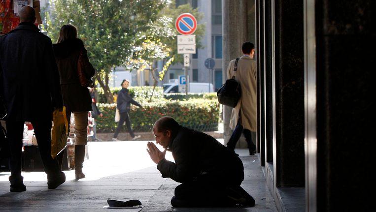 Man bedelt op de stoep voor een bank in Milaan. Beeld ap