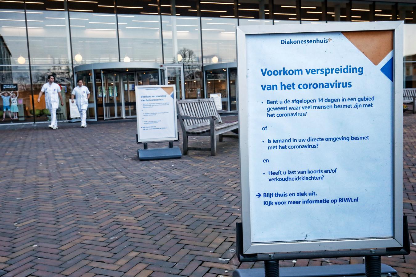 Richting de ingang van het Diakonessenhuis staan meerdere borden met informatie over verspreiding van het coronavirus.