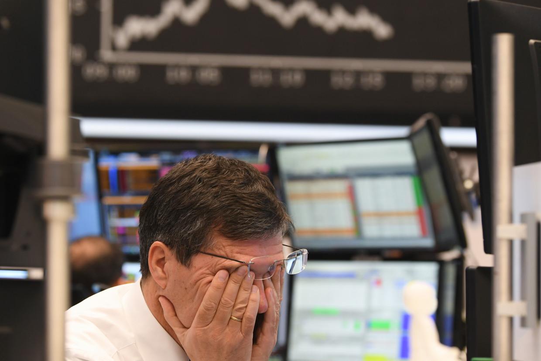 Een beurshandelaar van Frankfurt Stock Exchange wrijft zich in de ogen. De beurzen kleurden bloedrood nadat de olieprijzen daalden.