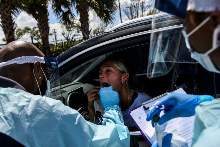 In Miami wordt een vrouw getest door medisch personeel in een drive-through. Beeld AFP