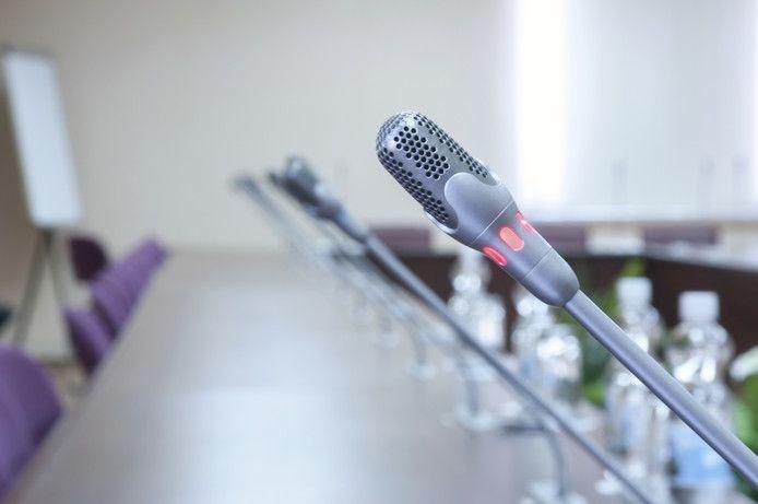 illustratie gemeenteraad politiek overleg microfoon