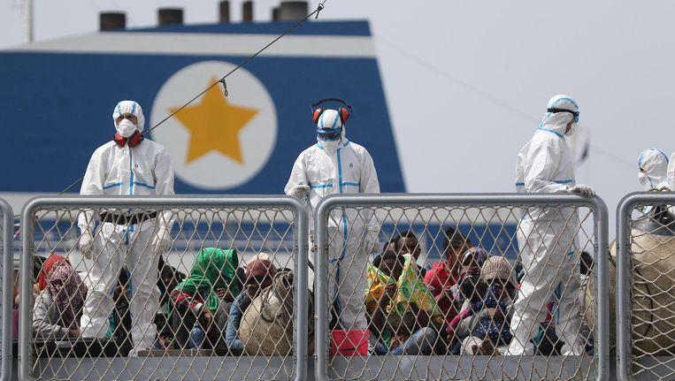 Migranten op een Italiaans fregat komen aan in de haven van Napels. Beeld EPA