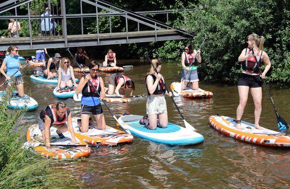 De deelnemers doen alle moeite om droog te blijven, niet altijd even handig onder de brug