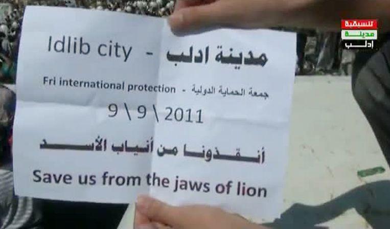 Still van een tv-fragment waarop een demonstrant een pamflet tegen het Syrische regime toont. Beeld afp