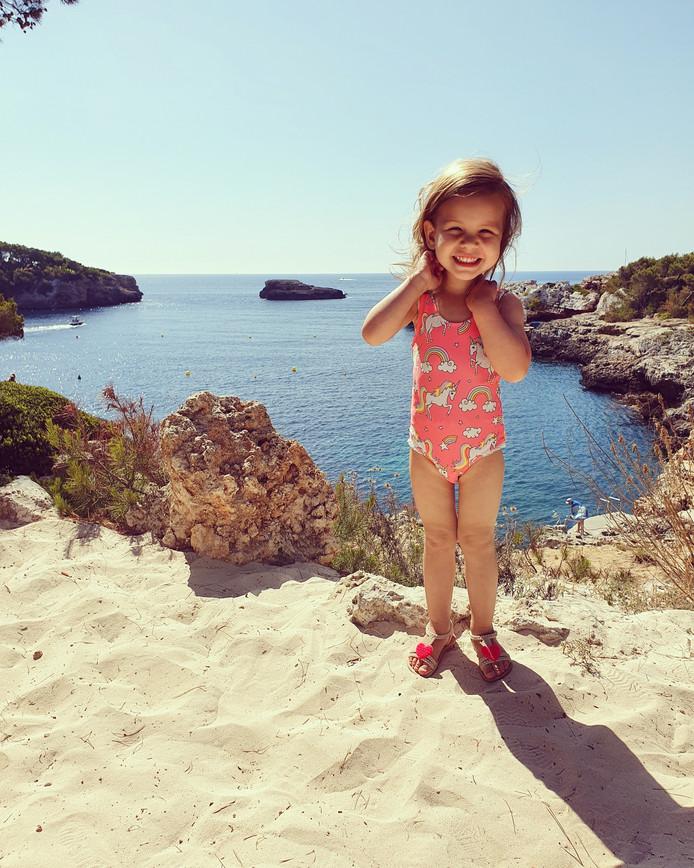 Romy Ramesar, de dochter van Robin, glundert als ze eenmaal op het strand van Cala D'or in Mallorca staat.