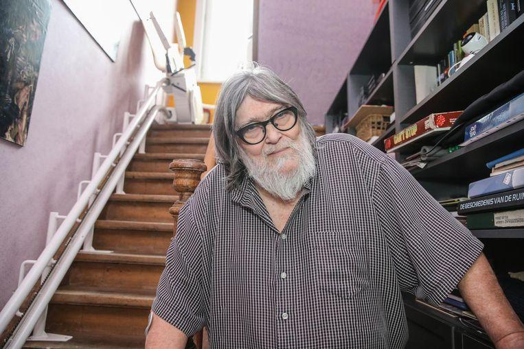 Patrick vandewalle bij de defecte traplift die in zijn huis werd geïnstalleerd.