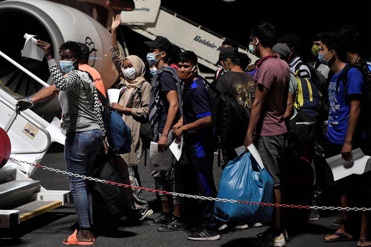 Minderjarigen uit het Moria-kamp worden met het vliegtuig naar andere kampen gebracht.  Beeld AFP