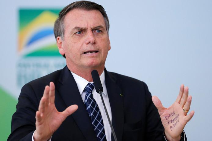 De Braziliaanse president Bolsonaro tijdens een toespraak. Op zijn linkerhand heeft hij drie steekwoorden geschreven: God, familie en Brazilië.