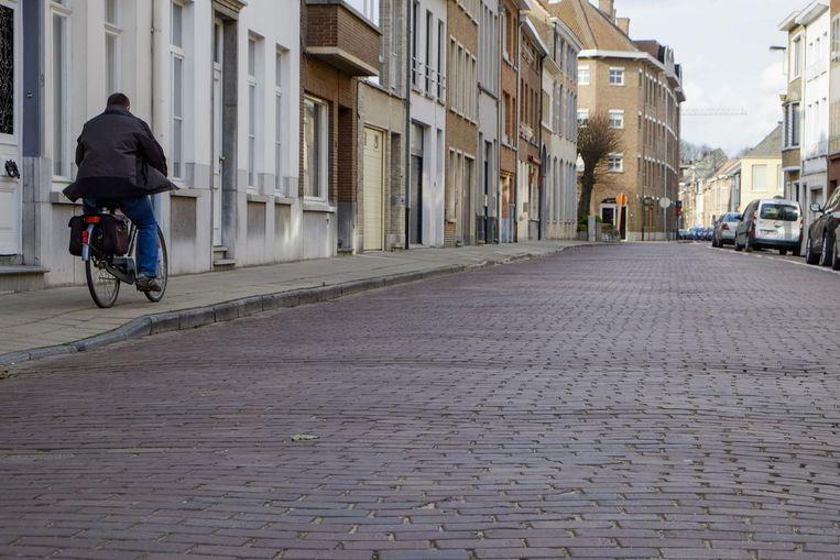 Een fietser rijdt over het voetpad in de Koning Albertstraat, die er lamentabel bijligt.