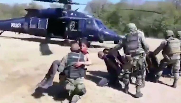 Een Mexicaanse soldaat tilt de zwaargewonde vrouw op om haar in de helikopter te zetten. Niet veel later zou ze sterven.