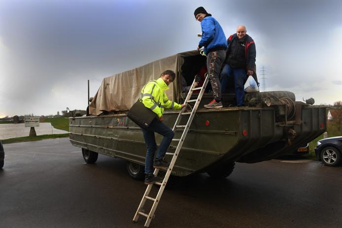 Personeel van Steenfabriek Schipperswaard in Echteld wordt met amfibievoertuig door de ondergelopen uiterwaarden gereden.