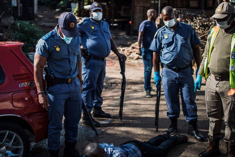 De Zuid-Afrikaanse politie arresteert een man in de Zuid-Afrikaanse hoofdstad Johannesburg omdat hij in het bezit is van bier, iets wat vanwege de lockdown verboden is.  Beeld AFP