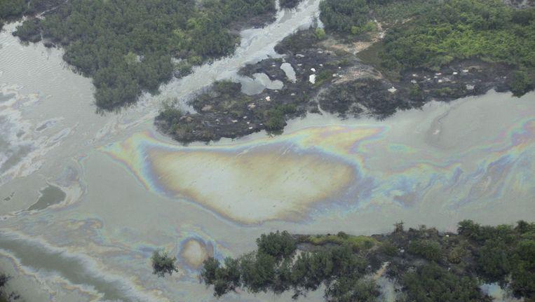 Olie in een kreek bij een illegale olieraffinaderij in het Nigeriaanse Ogoniland. Beeld ap