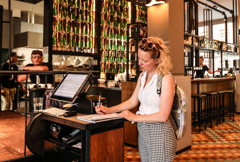Een klant vult het registratieformulier in bij Café de Jaren. Beeld Eva Plevier