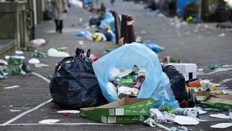 Achtergebleven vuilnis langs de grachten op de dag na de inhuldiging van koning Willem-Alexander. Beeld anp