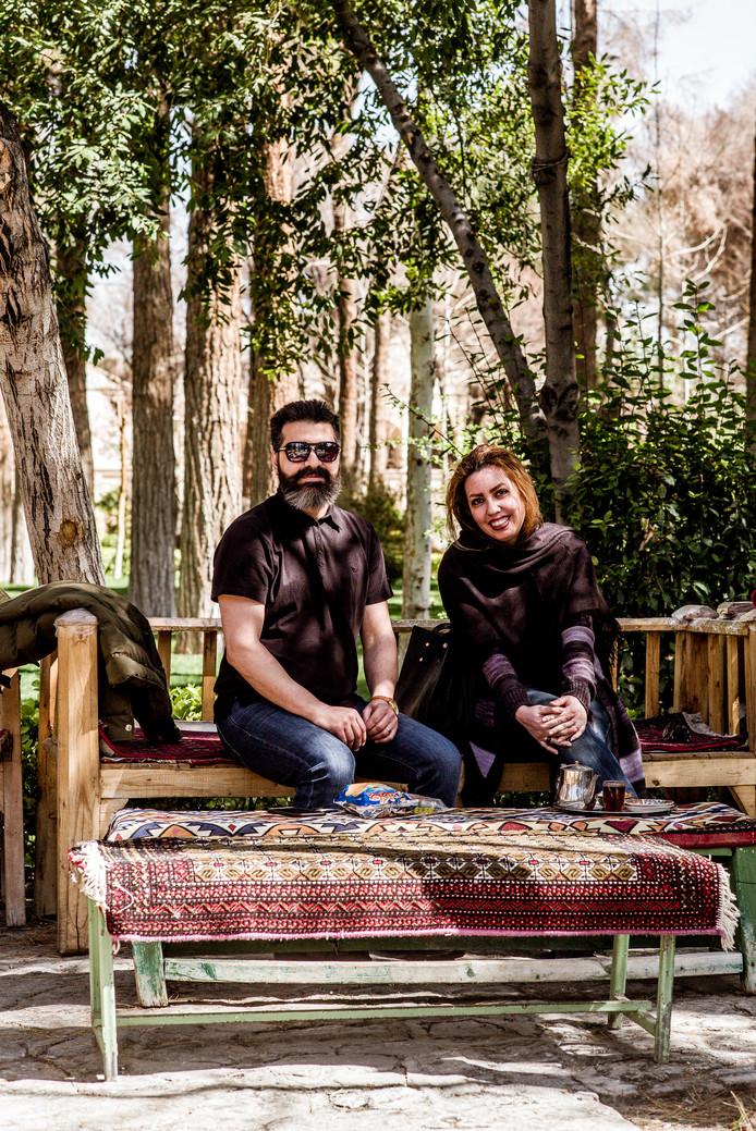 Bezoekers van het theehuis in de palmentuin van het Hasht Behesht paleis.