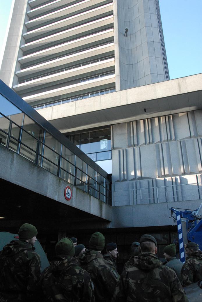 Militairen naast het Provinciehuis in afwachting van hun abseilexercitie, nog voor hun collega zijn been brak.