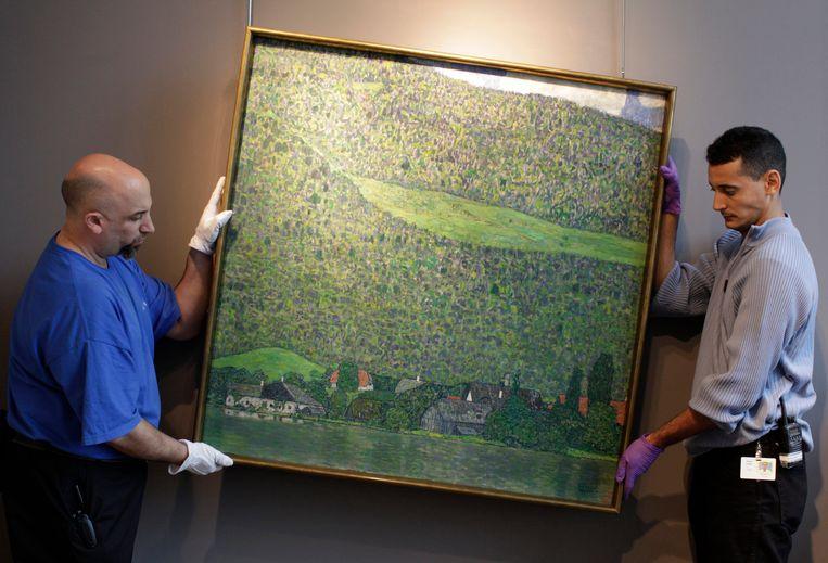 Medewerkers van veilinghuis Sotheby's in New York hangen het schilderij van Klimt op ter bezichtiging. Beeld null