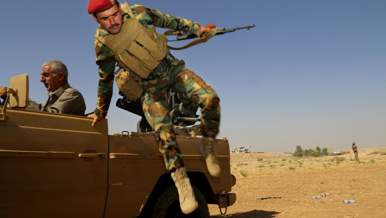 Een Koerdische peshmerga-strijder springt uit een auto. Beeld getty