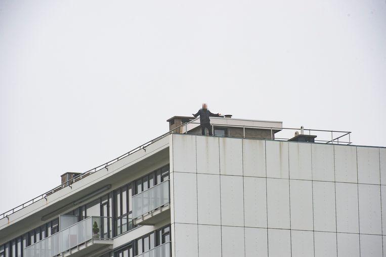 De man verschanst zich op het dak van het appartementsgebouw.