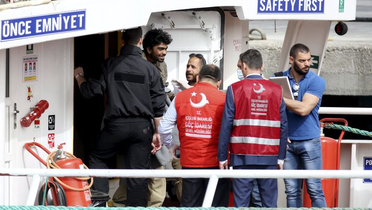 Een migrant verlaat onder escorte de boot waarmee hij naar Turkije is teruggebracht. Beeld reuters