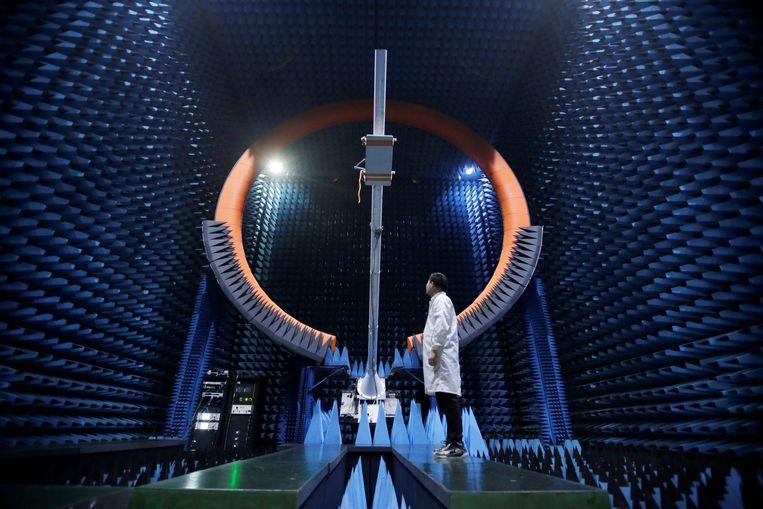 Een Huawei-ingenieur staat onder een 5G antenne. Beeld Reuters