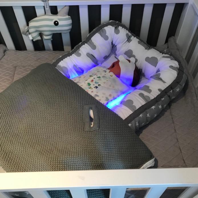 Baby thuis in een speciale slaapzak met lampjes.
