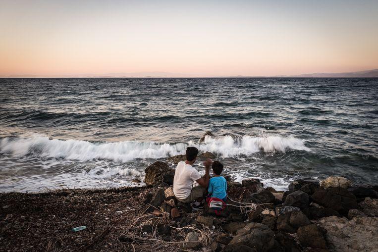 Een Afghaanse vader met zijn zoon aan het strand van Lesbos. Beeld Zolin Nicola