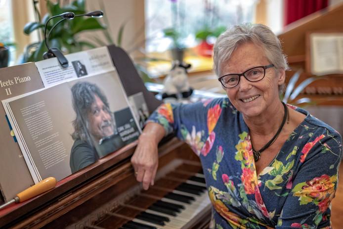 Marianne de Bruin aan de piano met een portret van haar man Dirk Jan.
