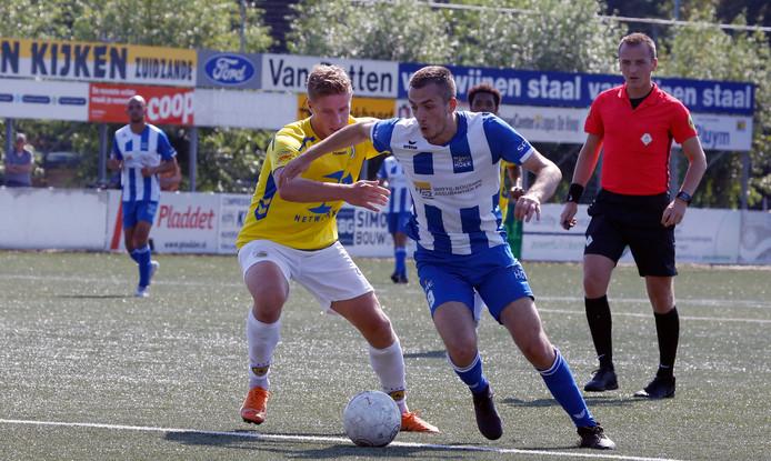 Ruben de Jager draait weg bij Lars Rauws van FC Lisse. Rechts scheidsrechter Roel de Cock uit Tilburg.