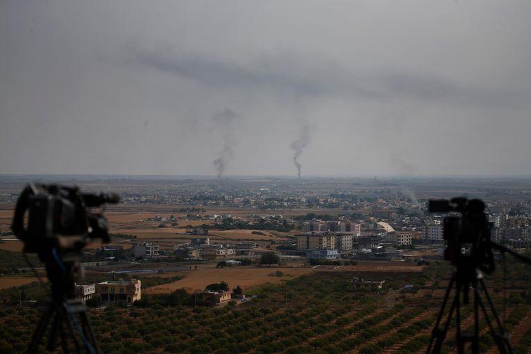 Rook kringelt op boven de grensstad Ras al-Ain. Deze foto is genomen vanaf de Turkse kant van de grens. Beeld AP