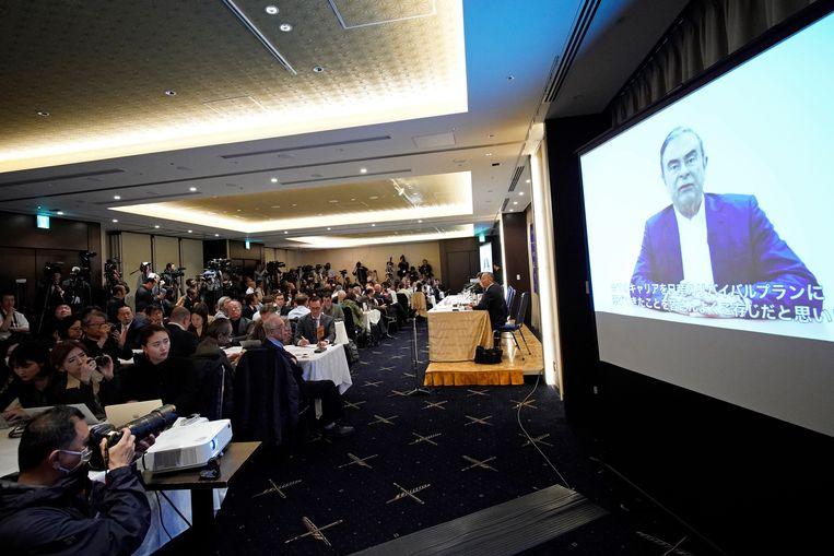 De pers bekijkt de videoboodschap van Carlos Ghosn op de Foreign Correspondents' Club of Japan in Tokio.