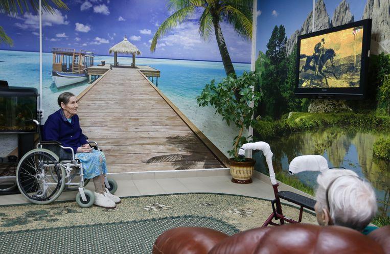Een vrouw kijkt televisie in een particulier bejaardentehuis in de Russische stad Rjazan, zo'n 200 kilometer ten zuidoosten van Moskou. Beeld Getty