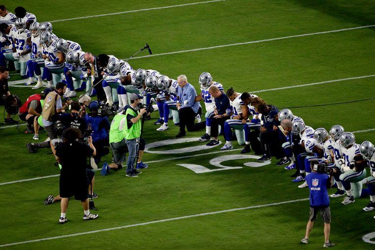 Dalles Cowboys-eigenaar Jerry Jones knielt op 25 september met zijn spelers tijdens het volkslied. Vorige week verplichte hij zijn spelers plotseling te blijven staan.  Beeld AP