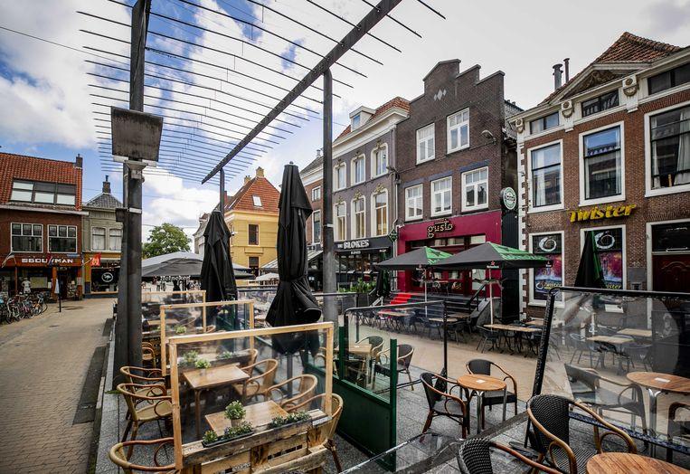 Terrassen met spatschermen in het centrum van de stad Groningen, in een van de regio's waar de alarmfase vanwege verspreiding van het coronavirus van waakzaam naar zorgelijk gaat.  Beeld ANP
