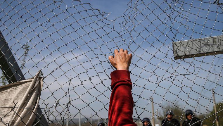 Een migrant probeert een hek bij een de Grieks-Macedonische grens te openen. Beeld REUTERS