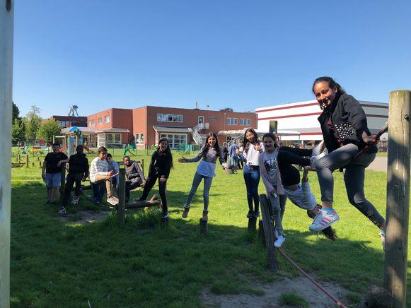 De leerlingen spelen in een groene omgeving.